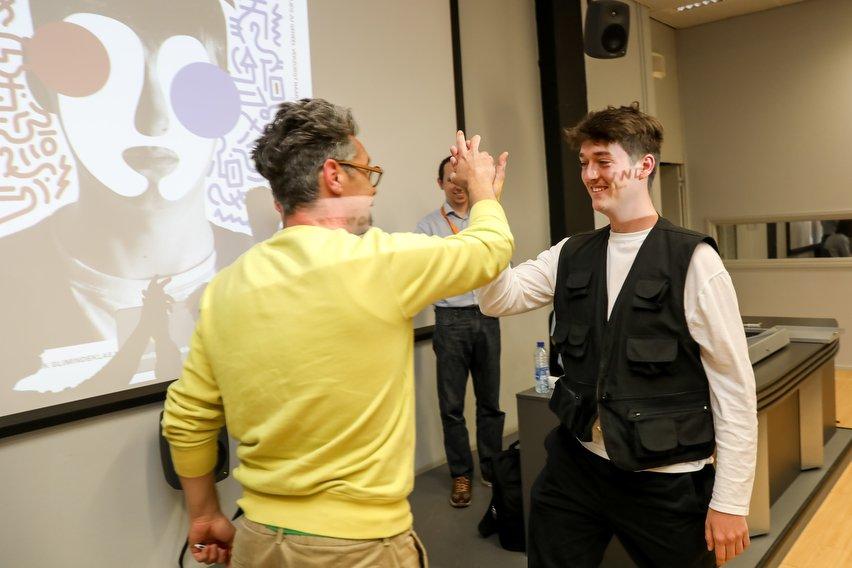 Juryvoorzitter Albert Hogeweg geeft winnaar Stijn high five